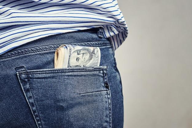 Notas de dólar em um bolso de trás das calças de brim Foto Premium