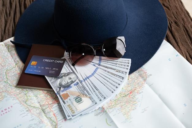 Notas de dólar, óculos de sol, cartão de crédito, passaporte e chapéu azul Foto gratuita