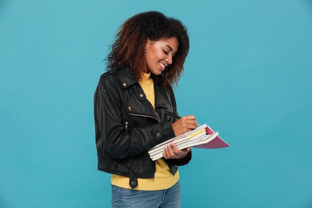 Notas de escrita feliz jovem estudante africano. Foto gratuita