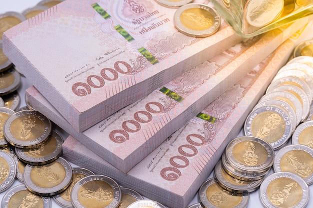 Notas e moedas de baht tailandês Foto Premium