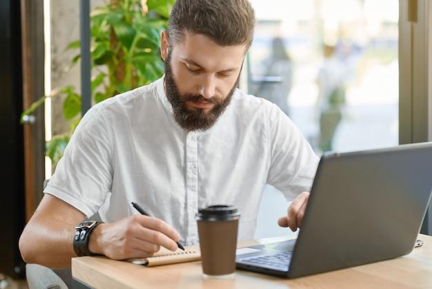 Notas farpadas da escrita do homem, trabalhando com o portátil que senta-se perto da janela. Foto Premium
