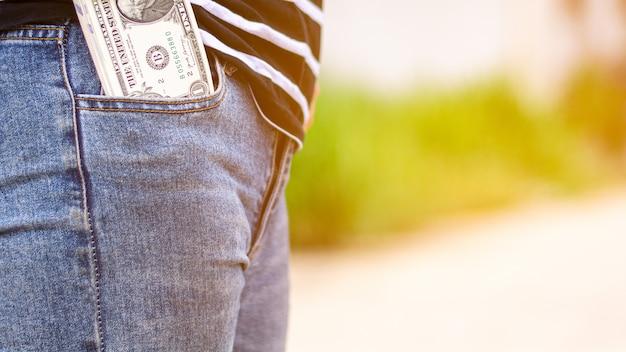 Notas no bolso da calça jeans de uma mulher. Foto Premium
