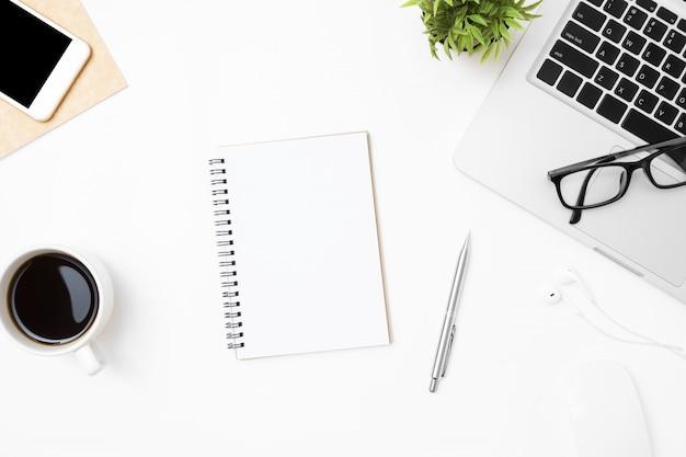 Notebook com a página em branco é no meio da mesa de mesa de escritório branco com suprimentos. Foto Premium