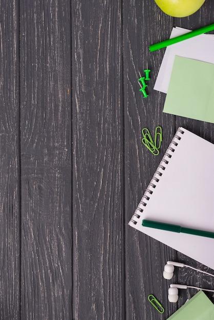 Notebook com clipes de papel e fones de ouvido na mesa de madeira Foto gratuita