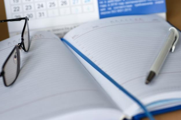 Notebook com um calendário para anotações na área de trabalho Foto Premium