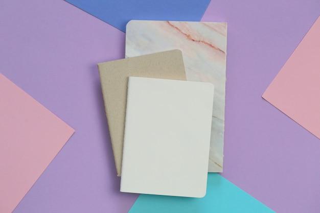 Notebook na tendência lilás rosa fundo gráfico. diários vazios em tons pastel da moda. plana leigos em cores pastel. vista superior, copie o espaço Foto Premium