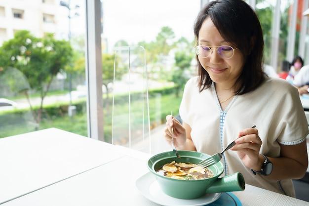 Nova mulher asiática de meia-idade normal comer alimentos com um prato de plástico para impedir a propagação Foto Premium