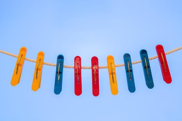 Nove prendedores de roupa de plástico pendurados no varal Foto Premium