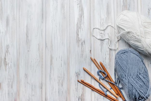 Novelos de fios e ganchos para tricô em uma mesa de madeira. Foto Premium