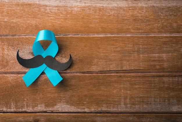 Novembro, azul, fita azul claro com um bigode masculino em fundo de madeira, conscientização sobre a saúde dos homens, conscientização sobre o câncer de próstata Foto Premium