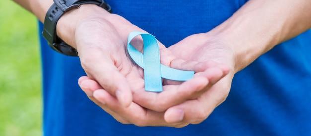 Novembro mês de conscientização do câncer de próstata, homem de camiseta azul com a mão segurando a fita azul para apoiar as pessoas que vivem e doenças. cuidados de saúde, homens internacionais, conceito do dia do câncer pai e mundial Foto Premium