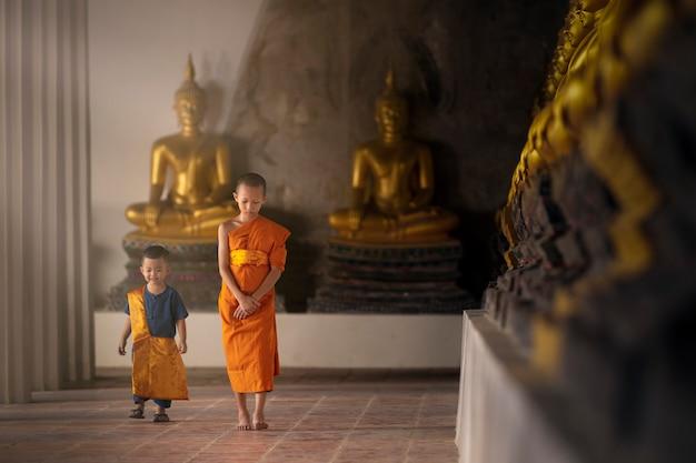 Noviços e assistentes caminham pacificamente em um templo com muitas imagens douradas de buda. Foto Premium