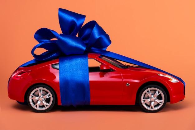 Novo carro vermelho com um laço azul como um presente em coral Foto Premium
