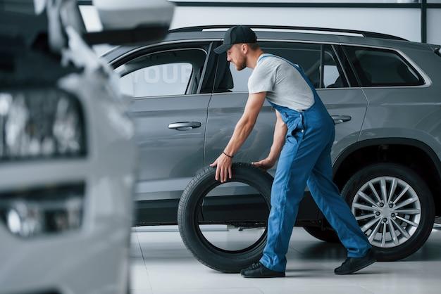 Novo. mecânico segurando um pneu na oficina. substituição de pneus de inverno e verão Foto gratuita