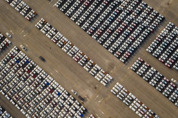 Novos carros alinhados no estacionamento para distribuição internacional para venda de negócios por grande corgo container transporte marítimo aberto Foto Premium