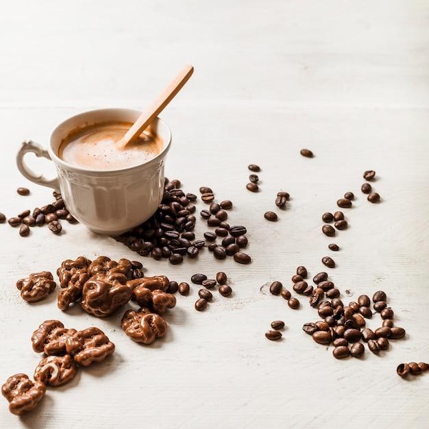 Noz de chocolate; grãos de café torrados e xícara de café sobre fundo de madeira Foto gratuita