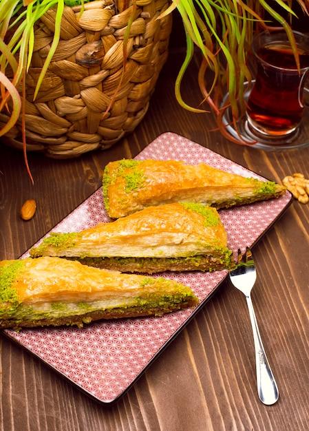 Noz, pistachio turkish estilo antep apresentação baklava e serviço Foto gratuita