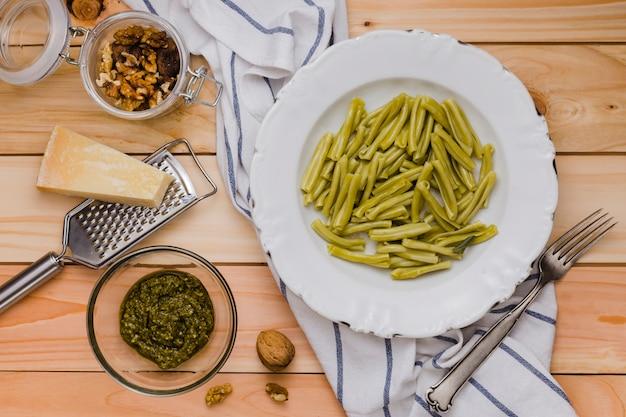 Noz; queijo; espinafre gemelli macarrão e molho na mesa de madeira Foto gratuita