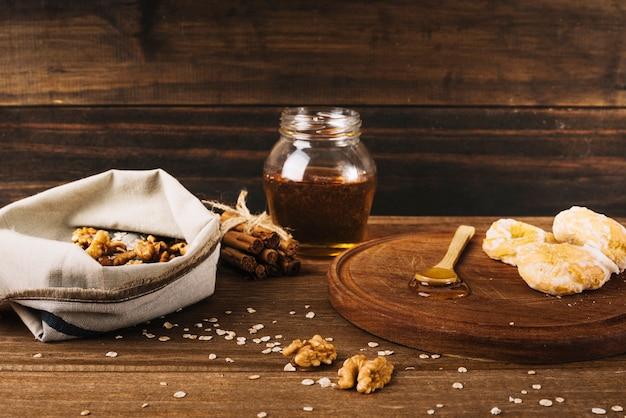 Noz; rosquinha; mel e canela na superfície de madeira Foto gratuita