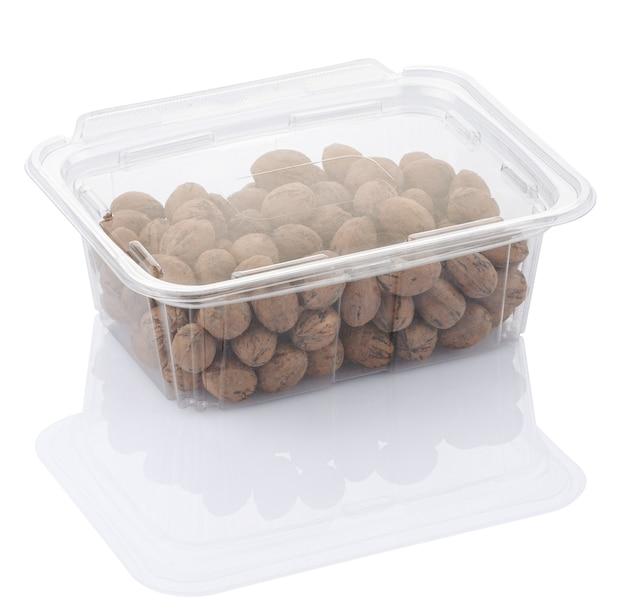 Nozes de noz-pecã em uma caixa de comida de plástico transparente isolada com traçado de recorte Foto Premium