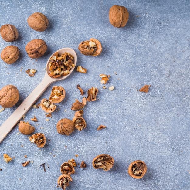 Nozes quebradas e kernel na colher de madeira sobre o pano de fundo texturizado Foto gratuita