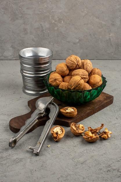 Nozes saborosas inteiras e descascadas, juntamente com vidro de metal em um cinza Foto gratuita
