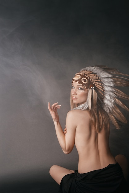 Nua mulher perfeita no traje de índios americanos na fumaça Foto Premium