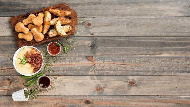 Nuggets de frango e fatias de batata na tábua de madeira Foto gratuita