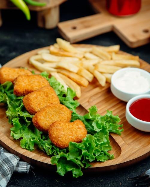 Nuggets de frango servidos com batata frita, ketchup e maionese Foto gratuita