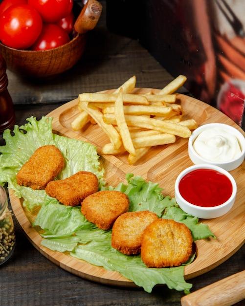 Nuggets fritos com batatas fritas na placa de madeira Foto gratuita