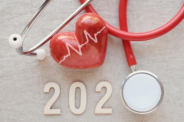 Número 2020 de madeira com estetoscópio vermelho. feliz ano novo para a saúde cardíaca e médica, seguro de vida Foto Premium