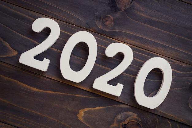Número 2020 para o ano novo em uma mesa de madeira. Foto Premium