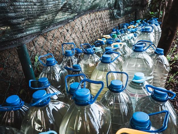 Número de garrafas plásticas cheias de água na frente da parede do jardim Foto gratuita