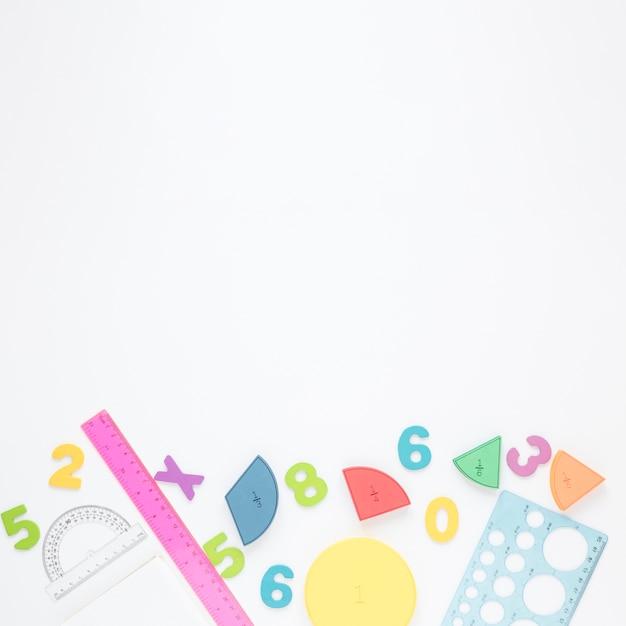 Números coloridos e artigos de papelaria em fundo branco, espaço de cópia Foto gratuita