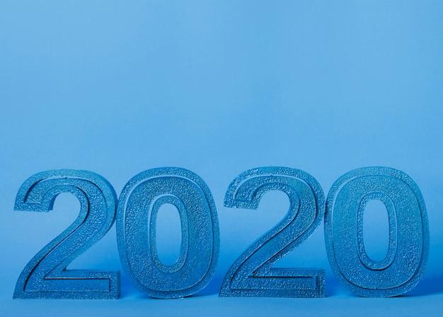 Números do ano novo 2020 em fundo azul com espaço de cópia Foto gratuita
