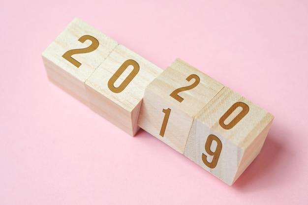 Números em cubos de madeira no fundo rosa. Foto Premium