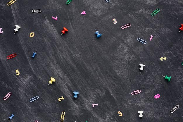 Números multicoloridos e clipes de papel com pinos espalhados na lousa Foto gratuita