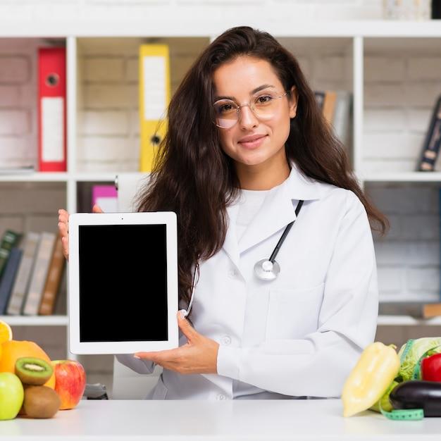 Nutricionista de tiro médio segurando um modelo de tablet Foto gratuita