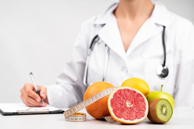 Nutricionista escrevendo e lanche de frutas saudáveis Foto gratuita