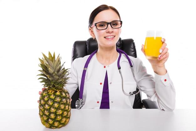 Nutricionista feminina sentado em seu local de trabalho, mostrando e oferecendo o copo de abacaxi suco fresco segurando abacaxi na mão em branco Foto Premium
