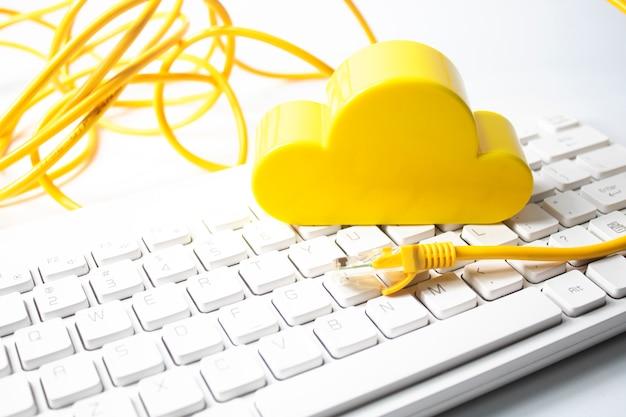 Nuvem amarela com fio lan e teclado no conceito de rede de negócios Foto Premium