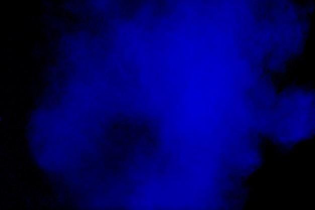 Nuvem de explosão de pó de cor azul no preto Foto Premium