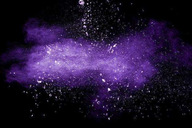 Nuvem de explosão de pó de cor roxa em fundo preto. respingo de partículas de poeira roxa. Foto Premium