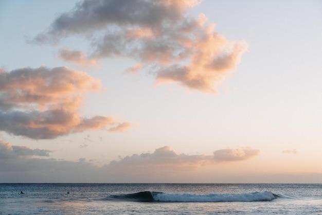 Nuvens brancas no céu com a luz do pôr do sol no oceano Foto gratuita