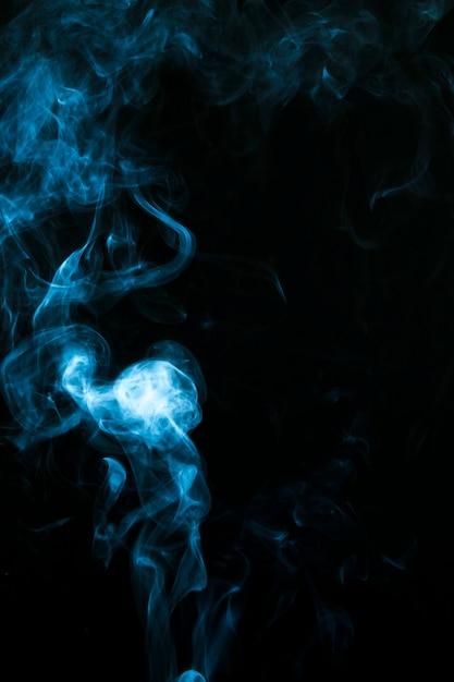 Nuvens de fumaça azuis sobre fundo preto Foto gratuita