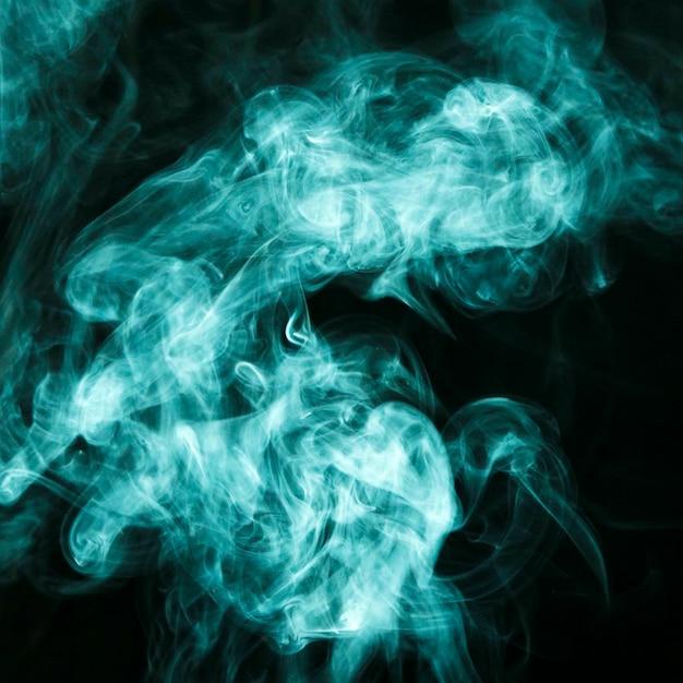 Nuvens de fumaça turquesa espalhar-se ampla contra o fundo preto Foto gratuita