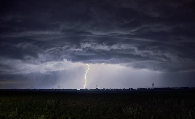 Nuvens irrealisticamente espessas e relâmpagos caem no chão Foto Premium