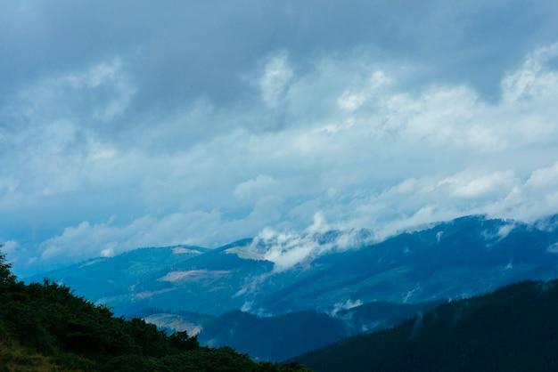 Nuvens sobre a montanha coberta de árvores verdes Foto gratuita