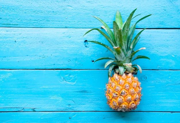 O abacaxi de verão no fundo de madeira azul. Foto Premium