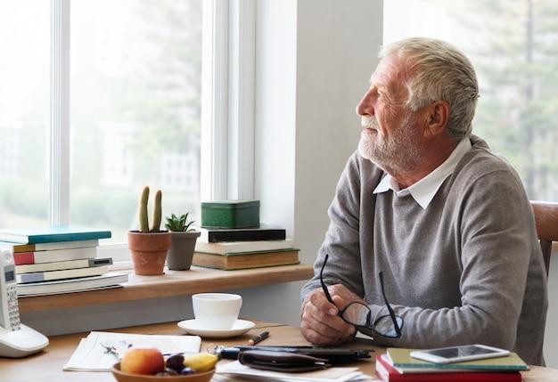 O adulto sênior que olha a janela exterior relaxa o conceito Foto Premium